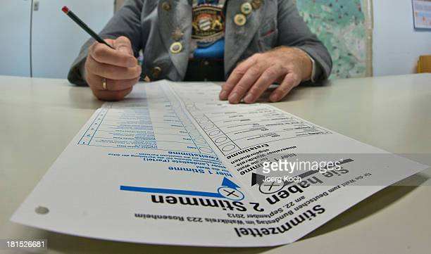 A man in a traditional Bavarian dress fills out his card in a voting booth before he casts his vote in the federal elections at the 'Schoenau...