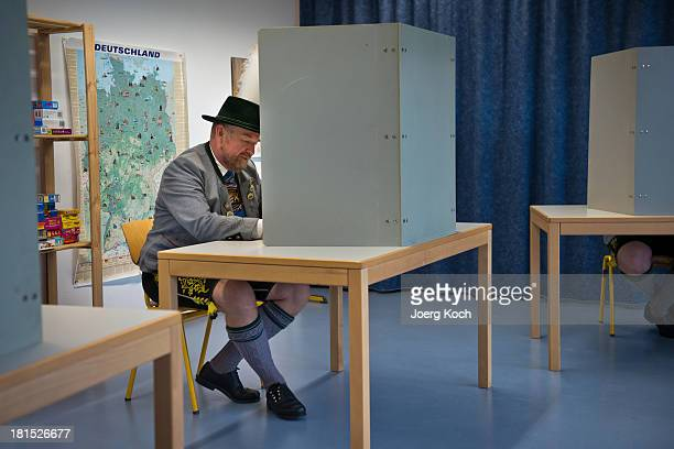 A man in a traditional Bavarian dress sits in a voting booth as he casts his vote in the federal elections at the 'Schoenau Grundschule' polling...