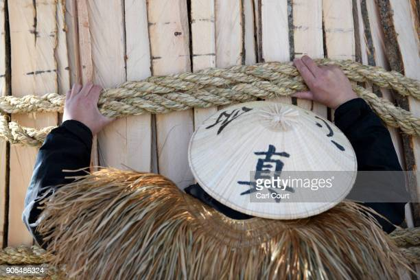 A man in a traditional conical hat and straw cape adjusts rope during construction of the shrine during preparations for the Nozawaonsen Dosojin Fire...