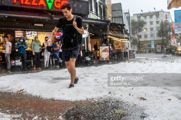 Man in a t-shirt and shorts walks across hailstones in Kadikoy, as heavy rains and hail lashed Istanbul, on September 29, 2020.