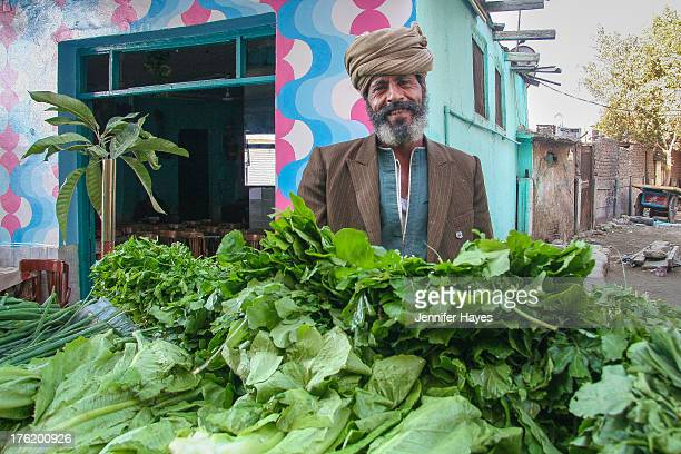 Man in a turban sells leafy green vegetables in the town of Port Said