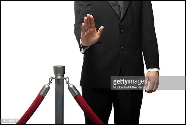 man in a tuxedo denying entry through a velvet rop - ロープ仕切り ストックフォトと画像
