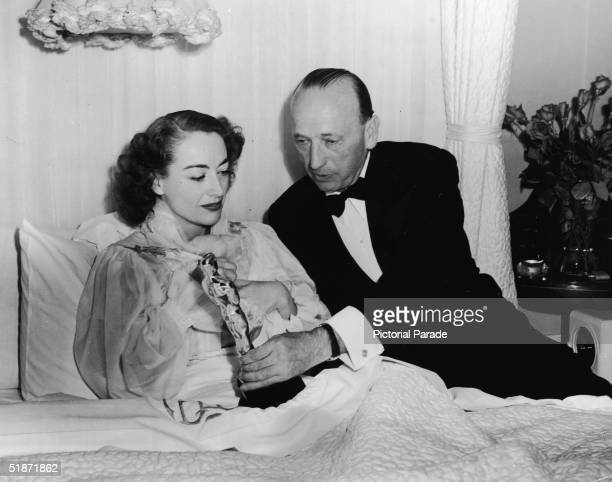 A man in a tuxedo presents the Best Actress Academy Award to American actress Joan Crawford for her performance in 'Mildred Pierce' as she lies in...