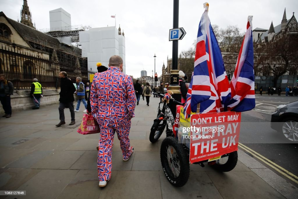 A man in a Union Flag suit walks past a cycle trailer with Union