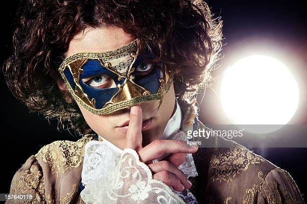 A man in a Venetian mask putting a finger to his mouth