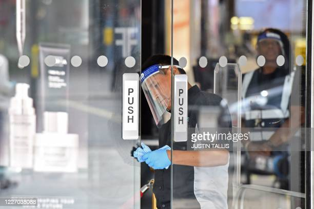 Man in a visor cleans the doors of Debanhams as a precaution against the transmission of the novel coronavirus on Oxford Street in London on July 14,...