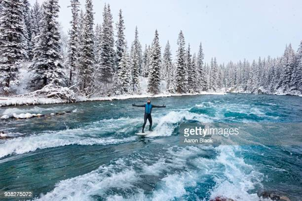 man in a wetsuit standing on surfboard with arms out surfing a turquoise wave in the middle of a river during a snowstorm. - kananaskis country stock pictures, royalty-free photos & images