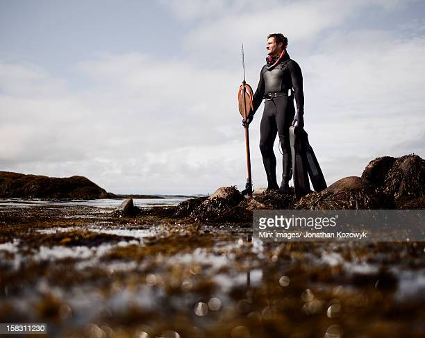 a man in a wetsuit, standing on the shore with a large spear fishing harpoon. - spear stock photos and pictures