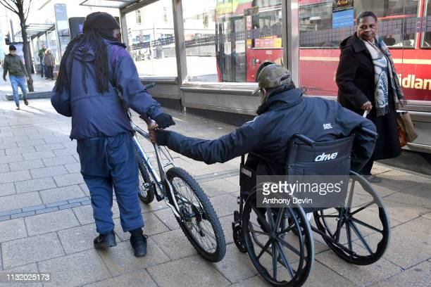 Man in a wheelchair holds onto a bicycle seat as he is pulled up a hill in central Birmingham on January 01, 2019 in Birmingham, England.