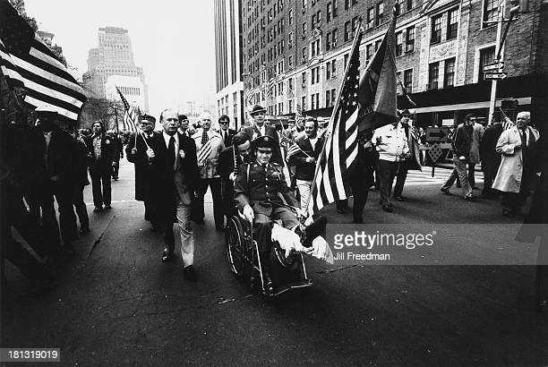 A man in a wheelchair is helped along in the 'Home With Honor' parade to mark the homecoming of American troops from Vietnam New York City 1973