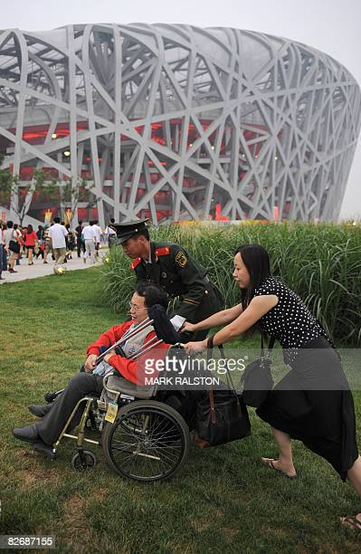 Man in a wheelchair is helped around some stairs as he arrives at the National Stadium before the opening ceremony of the 2008 Beijing Paralympic...