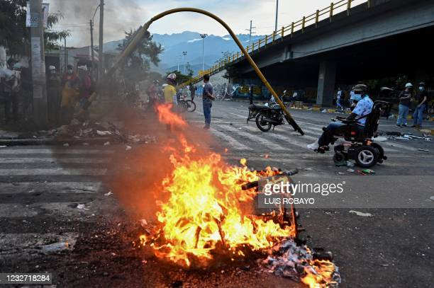 Man in a wheelchair passes a burning barricade blocking a street during a protest against President Ivan Duque's government in Cali, Colombia on May...