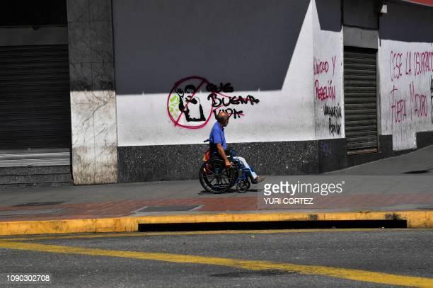 A man in a wheelchair passes by a graffiti against Venezuela's President Nicolas Maduro in Caracas on January 27 2019 Venezuela's President Nicolas...