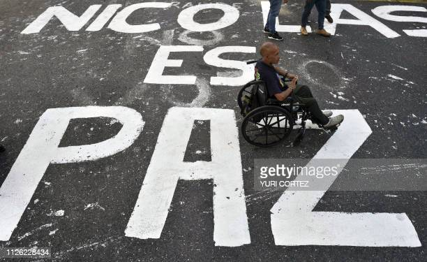 A man in a wheelchair remains over a legend painted on the street reading 'Nicolas is Peace' during an 'antiimperialist day' in support of Venezuelan...