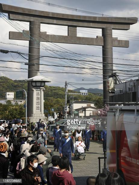 Man in a wheelchair takes part in the Tokyo Olympic torch relay against the backdrop of a shrine gateway in Sakurai in Nara Prefecture, western...