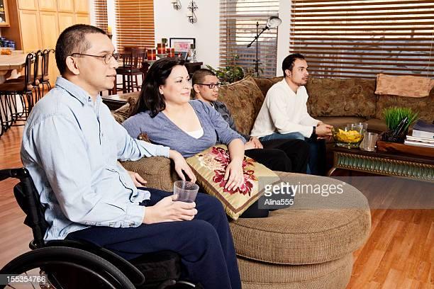 hombre en una silla de ruedas con su familia mientras disfruta de la televisión - quadriplegic fotografías e imágenes de stock