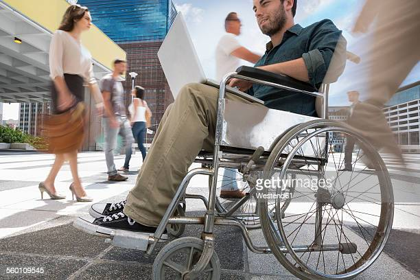 Man in a wheelchair working on his laptop between a crowd of people in a city