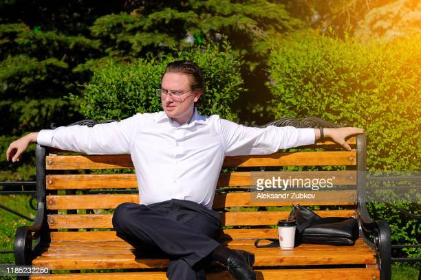 a man in a white shirt sits on a park bench on a summer day. - white shirt stock pictures, royalty-free photos & images