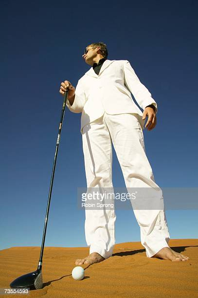 Man in a White Suit Holding a Golf Club on a Barren Desert Dune