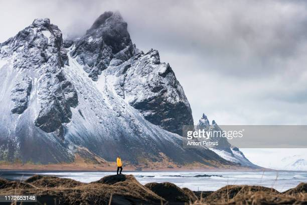 man in a yellow jacket on the background of vestrahorn mountain. iceland - islanda foto e immagini stock