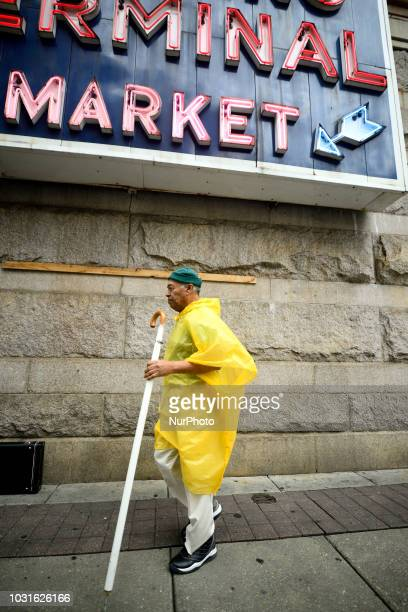 A man in a yellow poncho walks under the sign of Reading Terminal market in Philadelphia PA on September 11 2018