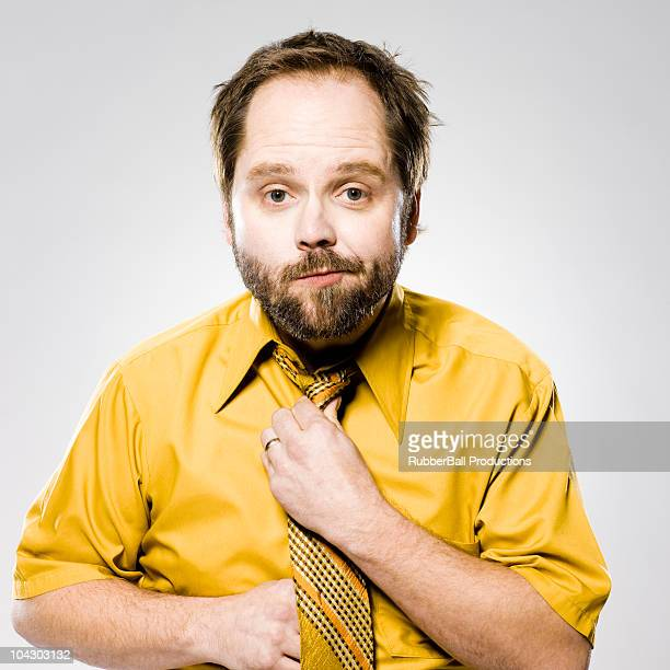 man in a yellow shirt and tie fixing his tie - adjusting necktie stock pictures, royalty-free photos & images