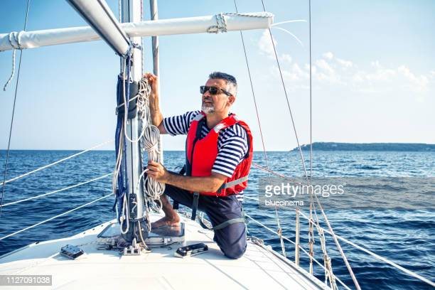 man in action of pulling rope - life jacket stock pictures, royalty-free photos & images