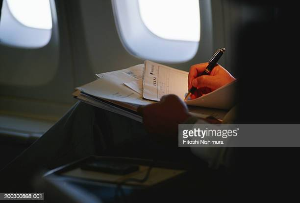 Man in aeroplane writing, mid section