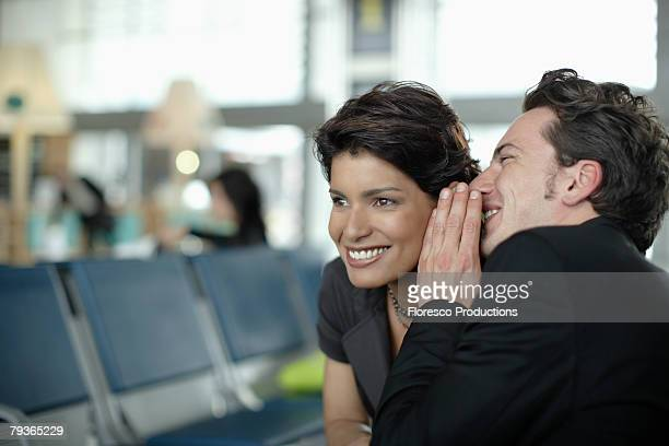 man in airport whispering in woman's ear - gossip stock pictures, royalty-free photos & images
