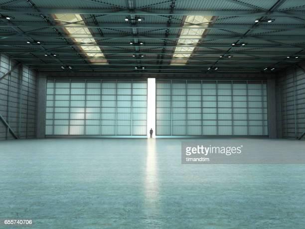 Man in an empty warehouse with door open