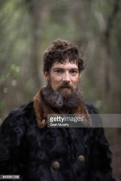 Man in Animal Skin Coat Looking into Camera
