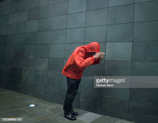 man in anorak struggling against wind, pulling hood over head - gale stock photos and pictures