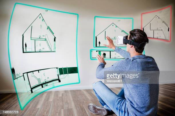 Man in apartment wearing VR glasses exploring house