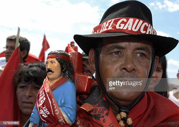 A man in Argentine gaucho attire carries an image of folk saint Gauchito Gil outside his sanctuary near Mercedes in the Argentine province of...