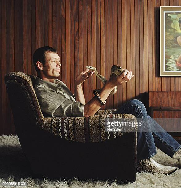 Man in arm chair holding boa constrictor, side view