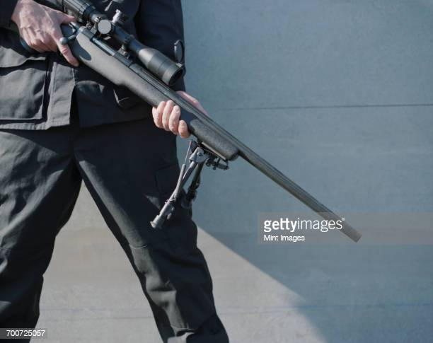 man in armed forces holding high powered sniper rifle - ライフル ストックフォトと画像