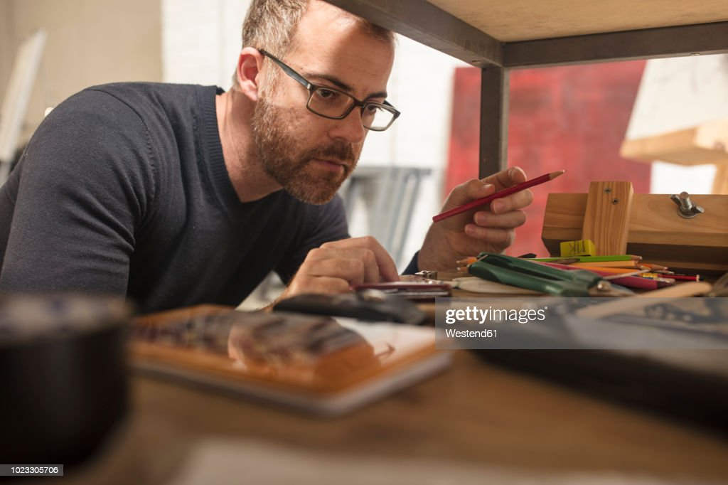Man in artist's studio checking supplies : Stock Photo