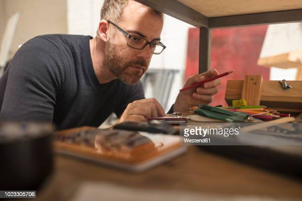 man in artist's studio checking supplies - museum curator stock pictures, royalty-free photos & images