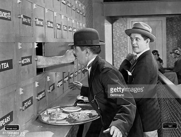 Man in automat after putting coins in machine receives a punch in the nose from an extended arm Undated movie still BPA2# 2038
