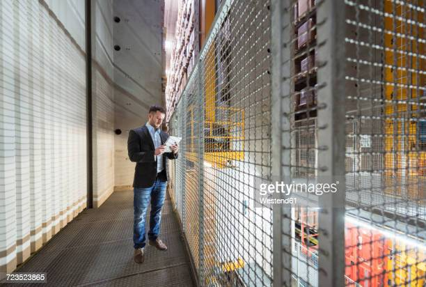 Man in automatized high rack warehouse looking at tablet