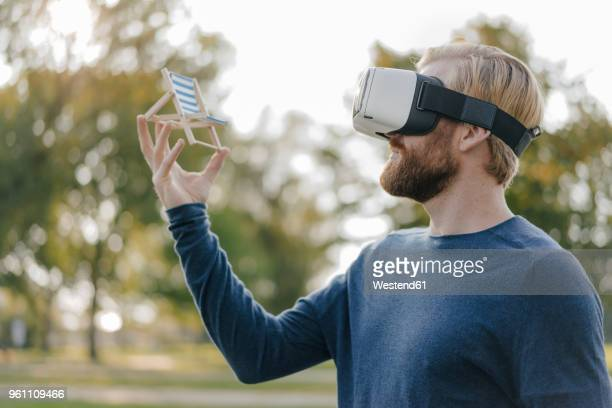 Man in autumnal park wearing Virtual Reality Glasses looking at miniature beach lounger