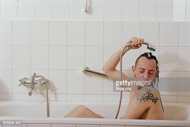 Man in bath, washing hair with shower head