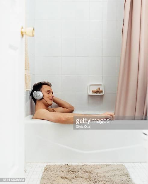 Man in Bath Wearing Headphones