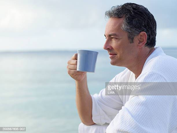Man in bathrobe drinking coffee in front of ocean