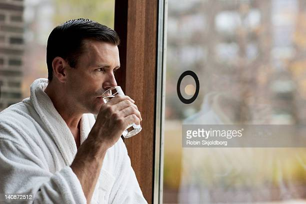 man in bathrobe drinking water by window - robin skjoldborg stock pictures, royalty-free photos & images