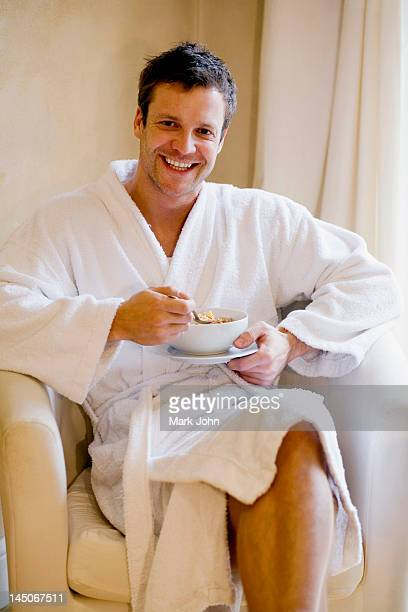 Man in bathrobe having bowl of cereal