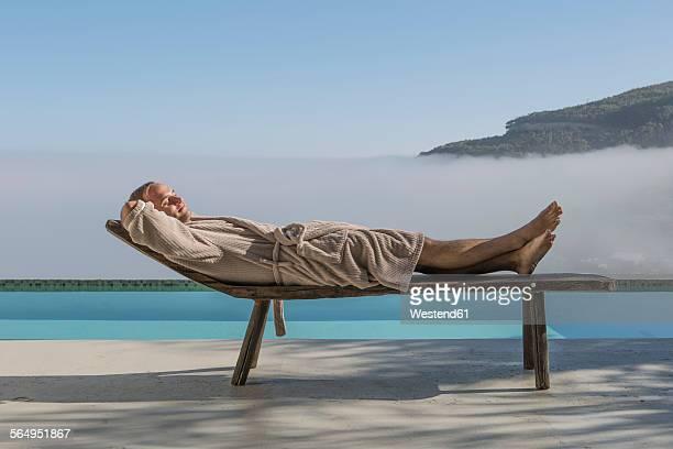 man in bathrobe lying on a lounge next to pool - cadeira recostável - fotografias e filmes do acervo