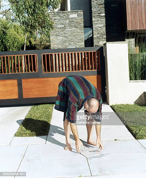 Man in bathrobe, picking up newspaper in front of house