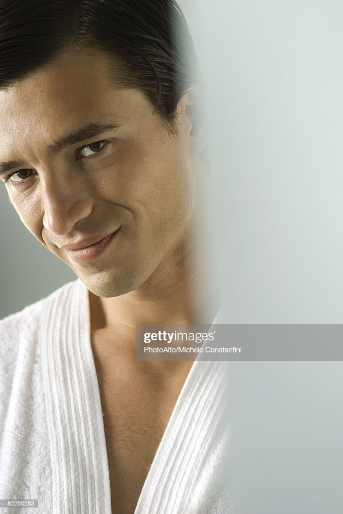 Man in bathrobe smiling at camera, portrait, cropped : Stock Photo