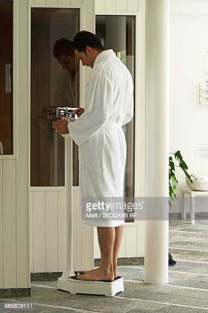 Man in bathrobe standing on scales